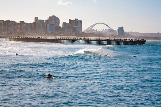 Surfing in Durban with Moses Mabhida Stadium in the distance. Photo by Mohammed Moosa